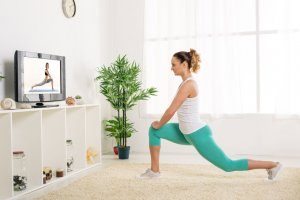 Image of woman exercising in front of the TV