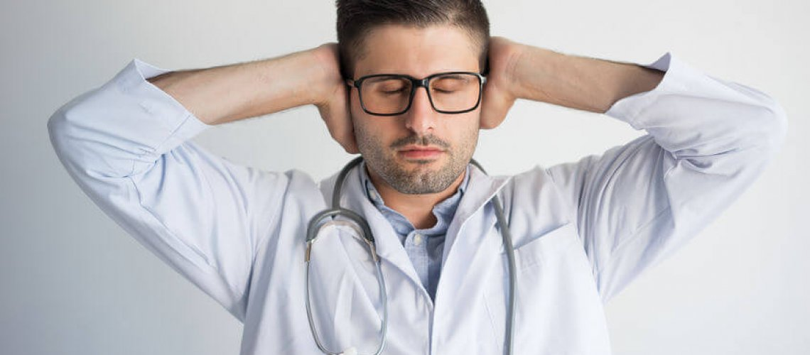 Portrait of tired young male general practitioner covering ears. Caucasian medic wearing glasses, lab coat and stethoscope with closed eyes. Do not want to hear concept