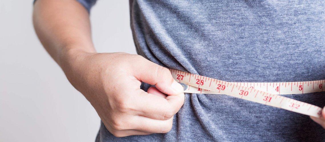 Image of woman checking her waistline