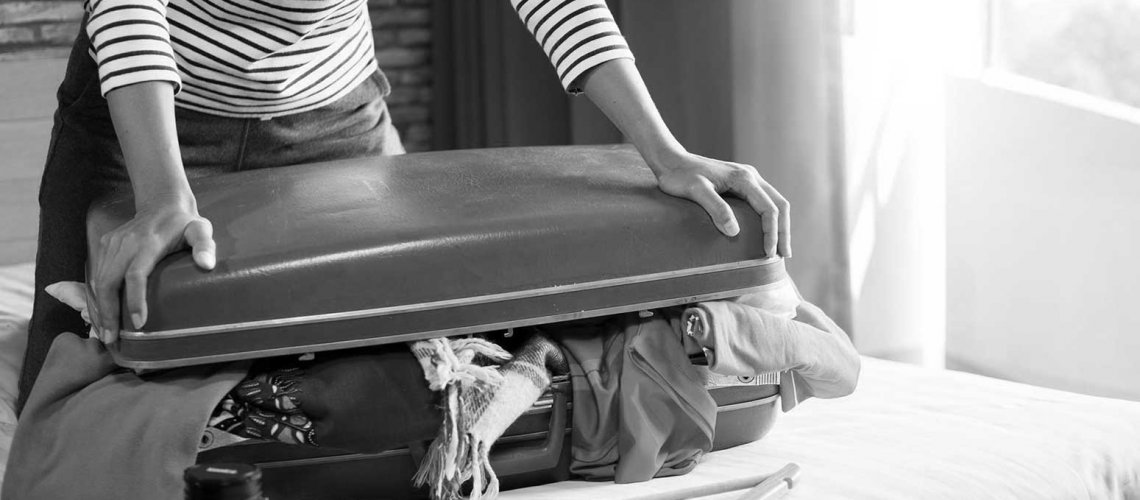 Image of person packing suitcase to travel abroad for weight loss surgery